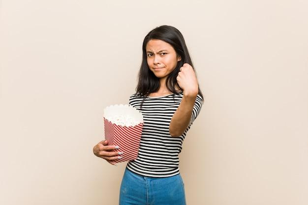 Молодая азиатская девушка держа попкорн ведро показывая кулак к камере, агрессивное выражение лица.