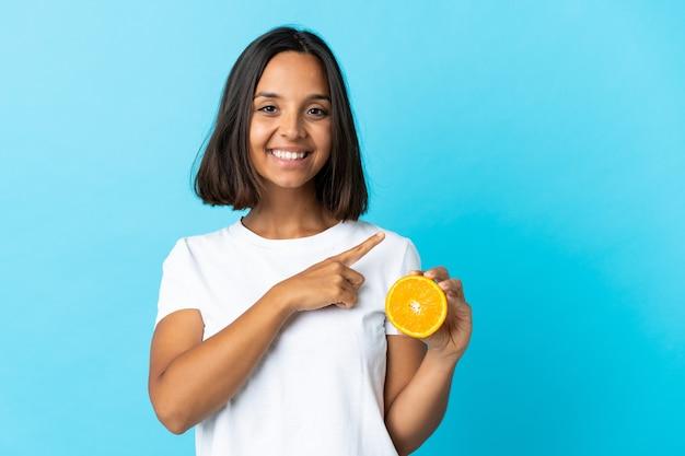 Молодая азиатская девушка держит апельсин на синем фоне, указывая в сторону, чтобы представить продукт