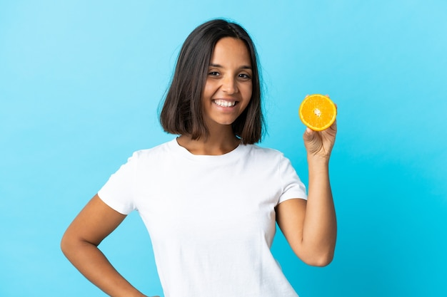 腰に腕と笑顔でポーズをとって青い背景に分離されたオレンジを保持している若いアジアの女の子