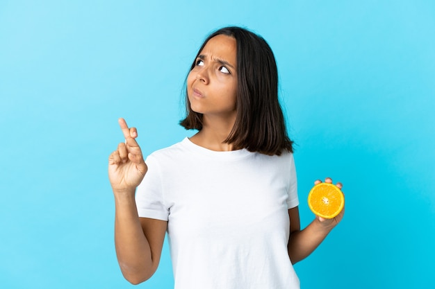 Молодая азиатская девушка держит апельсин на синем фоне со скрещенными пальцами и желает лучшего