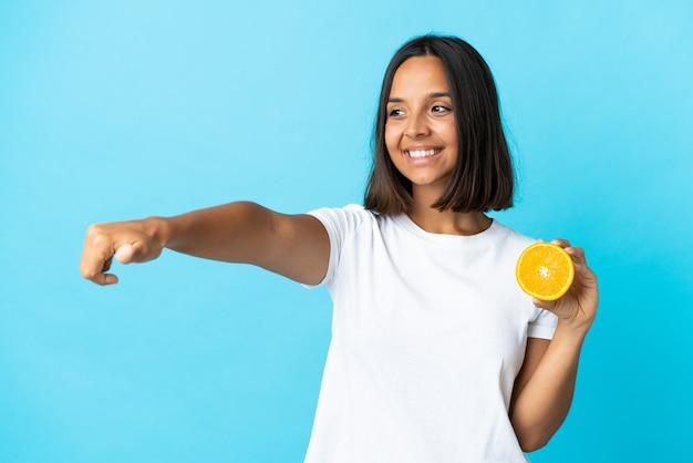 親指を立てるジェスチャーを与える青い壁に分離されたオレンジを保持している若いアジアの女の子