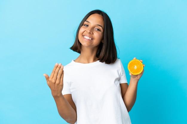 Молодая азиатская девушка держит апельсин на синей стене, приглашая прийти с рукой.