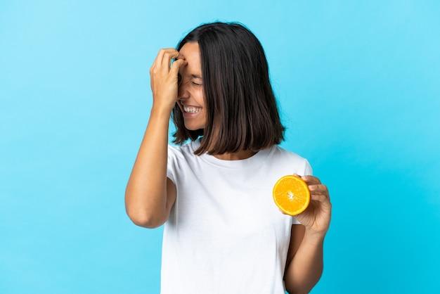 笑って青い壁に分離されたオレンジを保持している若いアジアの女の子