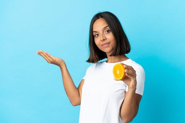 Молодая азиатская девушка держит апельсин на синем, протягивая руки в сторону, приглашая приехать