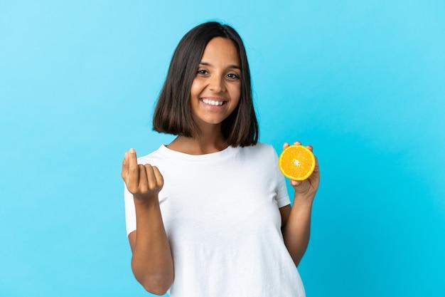 お金を稼ぐジェスチャーで青にオレンジを保持している若いアジアの女の子