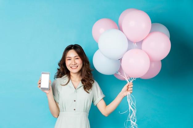 風船を持って、ターコイズで幸せな表情で電話を使用して若いアジアの女の子