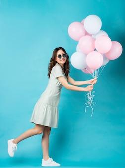 ターコイズで幸せな表情で風船を保持している若いアジアの女の子