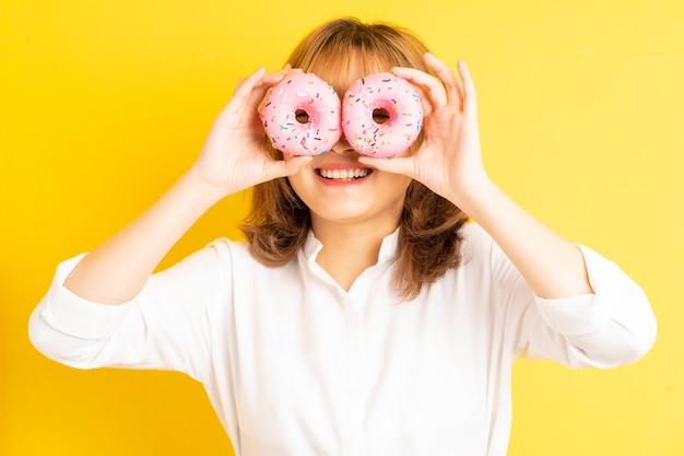 Молодая азиатская девушка держит пончик с веселым выражением лица на фоне
