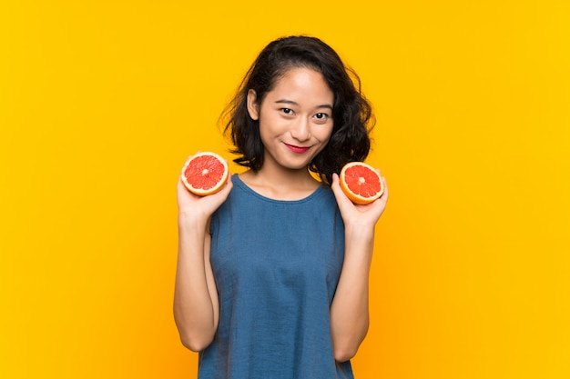 Young asian girl holding a grapefruit over isolated orange background