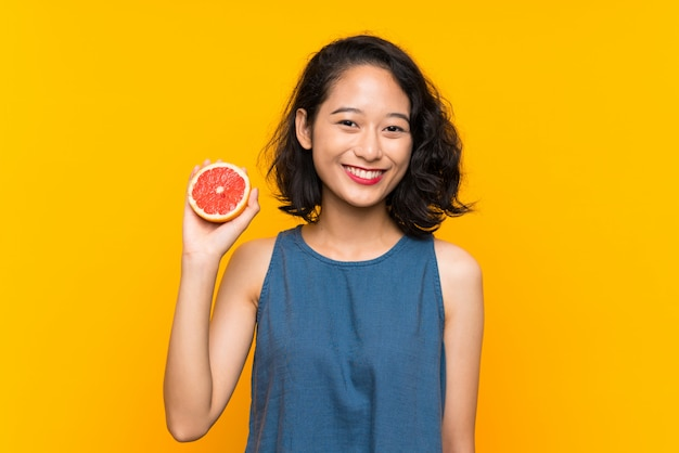Young asian girl holding a grapefruit over isolated orange wall smiling a lot