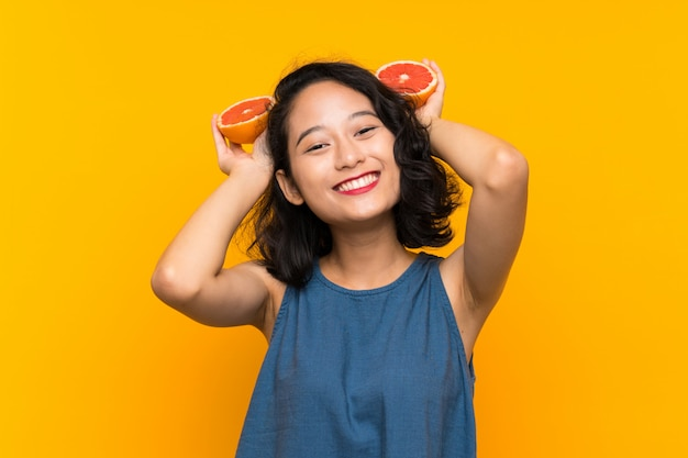Young asian girl holding a grapefruit over isolated orange wall