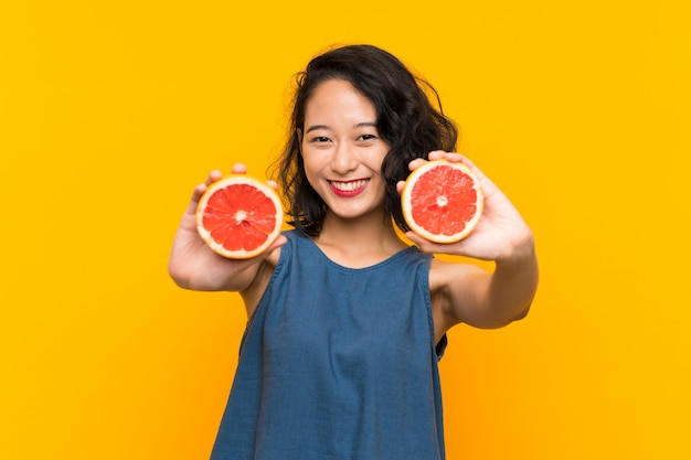 Young asian girl holding a grapefruit over orange wall