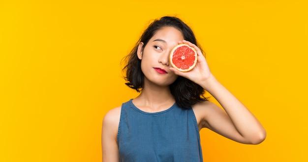 Young asian girl holding a grapefruit
