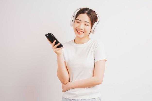 音楽を聴いて携帯電話を持っている若いアジアの女の子