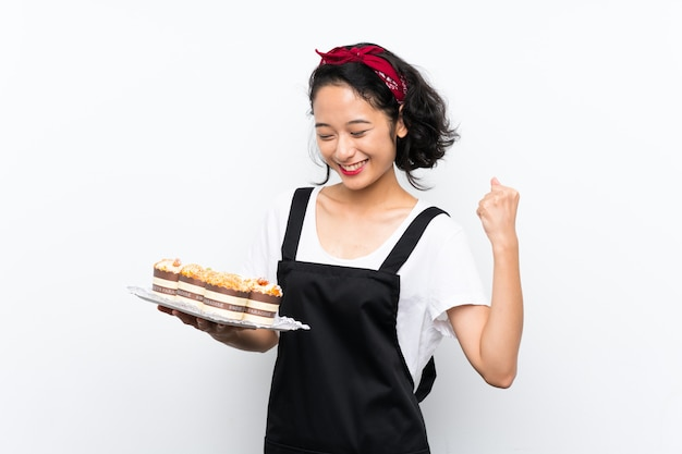 Young asian girl holding lots of muffin cake celebrating a victory