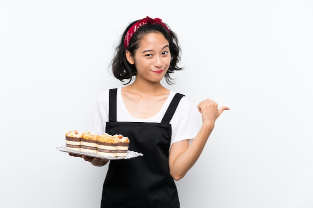 Young asian girl holding lots of muffin cake over isolated white wall pointing to the side to present a product
