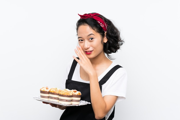 Young asian girl holding lots of muffin cake whispering something