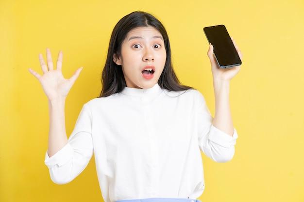 黄色の背景に表情と電話を保持している若いアジアの女の子