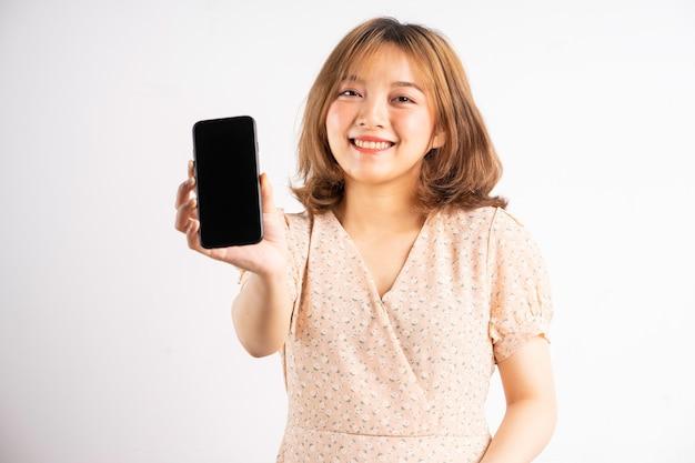식과 몸짓으로 전화를 들고 젊은 아시아 소녀