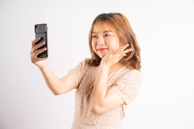 Young asian girl holding phone with expressions and gestures on white