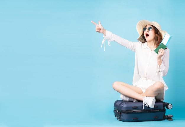 Молодая азиатская девушка держит билет на самолет и телефон, сидя на чемодане