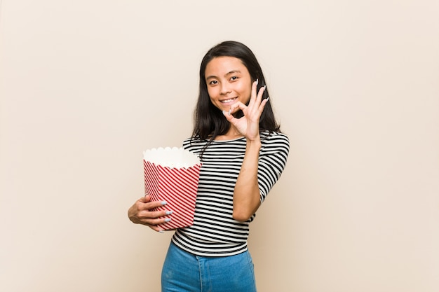 Young asian girl holding a popcorn bucket cheerful and confident showing ok gesture.