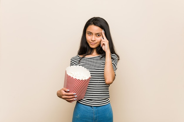Young asian girl holding a popcorn bucket pointing his temple with finger, thinking, focused on a task.