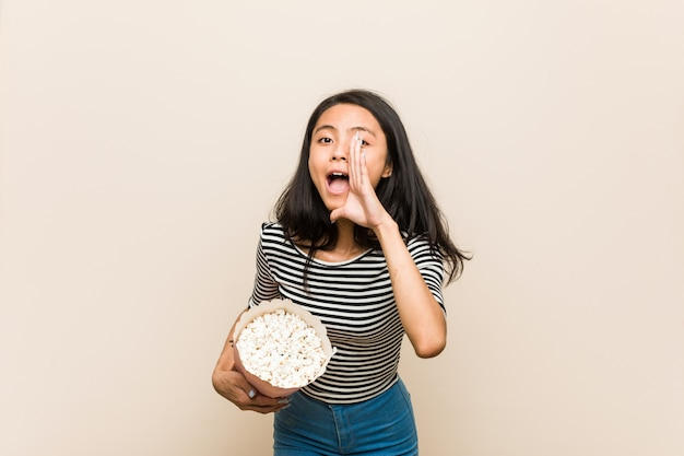 Young asian girl holding a popcorn bucket shouting excited to front.