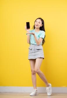 노란색에 스마트 폰 들고 젊은 아시아 소녀