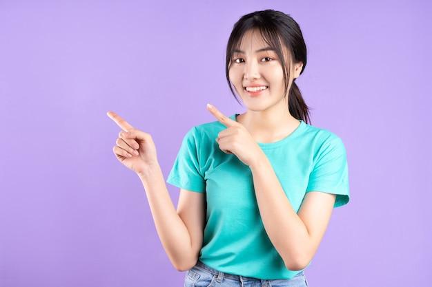 紫色の壁に電話を使用してシアンのシャツを着た若いアジアの女の子