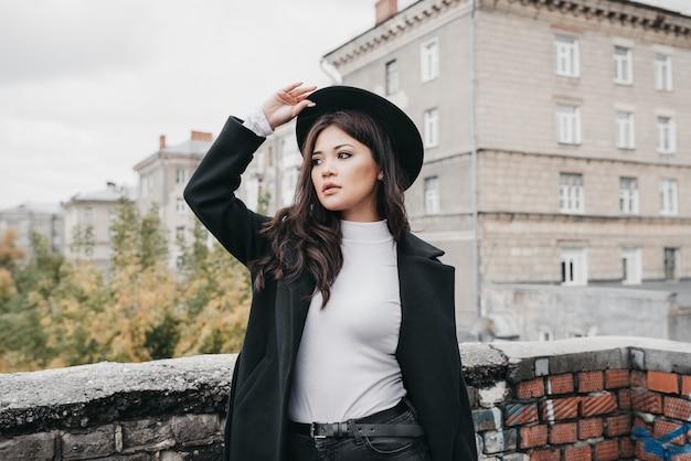Молодая азиатская девушка в темном пальто и шляпе