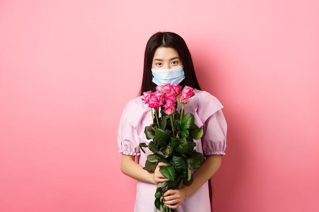 バレンタインデーに花を保持している医療マスクの若いアジアの女の子は、ピンクの背景に立って、恋人からバラの花束を受け取ります。社会的距離とcovid-19の概念。