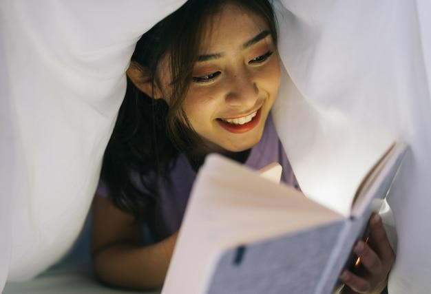 若いアジアの女の子は毛布に横たわって、本を読むために彼女のスマートフォンからの光を使用しています