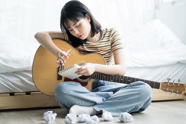 Молодая азиатская девушка занимается дома на гитаре и сочиняет музыку