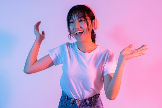 若いアジアの女の子は、ヘッドフォンを着用し、興奮して音楽を聴いています