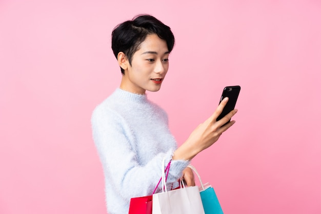 Young asian girl over isolated pink wall holding shopping bags and writing a message with her cell phone to a friend