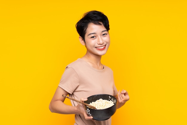 Young asian girl over isolated yellow wall and pointing it while holding a bowl of noodles with chopsticks