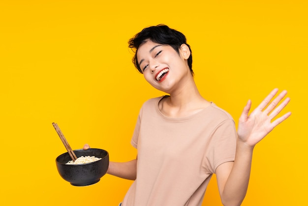 Young asian girl over isolated yellow wall saluting with hand with happy expression while holding a bowl of noodles with chopsticks