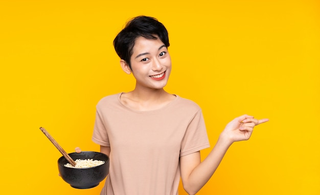 Young asian girl over isolated yellow wall surprised and pointing finger to the side while holding a bowl of noodles with chopsticks