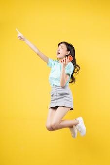 黄色にジャンプする若いアジアの女の子