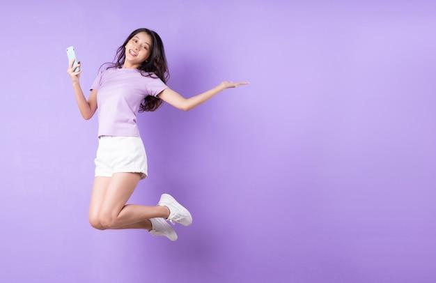 紫色の背景にジャンプする若いアジアの女の子