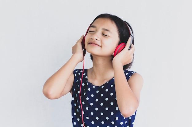 若いアジアの女の子は白のイヤホンから音楽を聴きます。