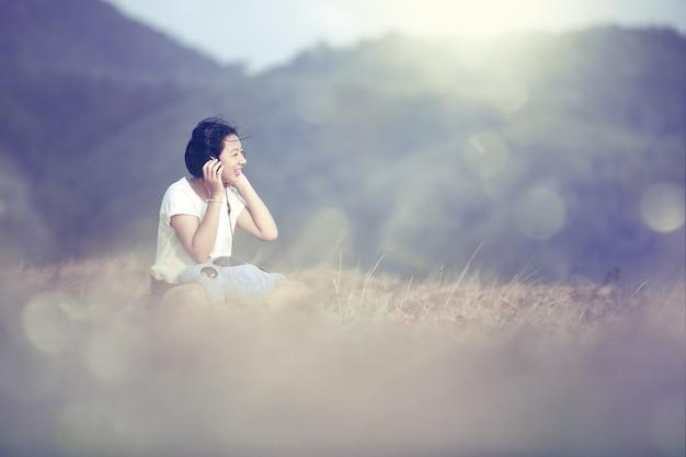 젊은 아시아 소녀 정원에서 헤드폰으로 음악을 듣고 음악을 들으면서 행복하고 웃고