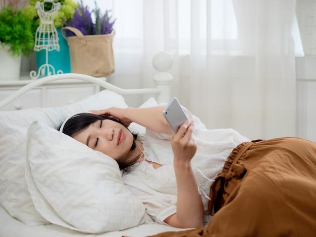 침대에서 음악을 듣고 젊은 아시아 여자