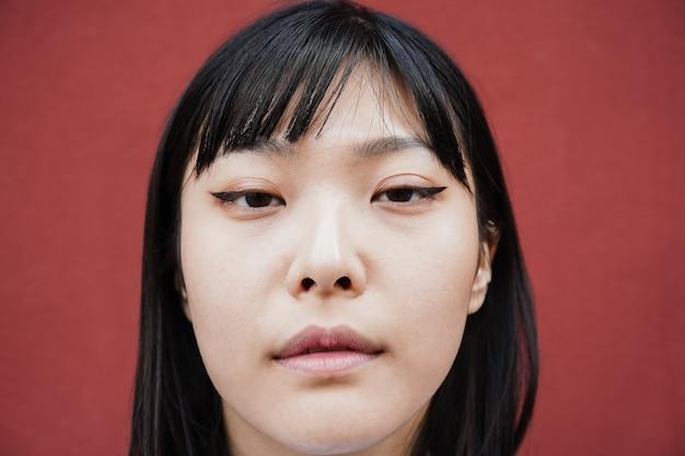 야외 카메라를 보고 있는 젊은 아시아 소녀 - 얼굴에 초점