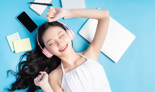 노트북, 스마트 폰, 헤드폰 및 메모와 함께 파란색에 누워 젊은 아시아 소녀