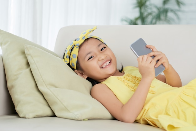 Young asian girl lying on sofa with smartphone, looking at camera and smiling