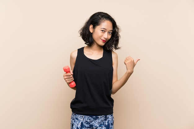 Young asian girl making weightlifting over isolated wall pointing to the side to present a product