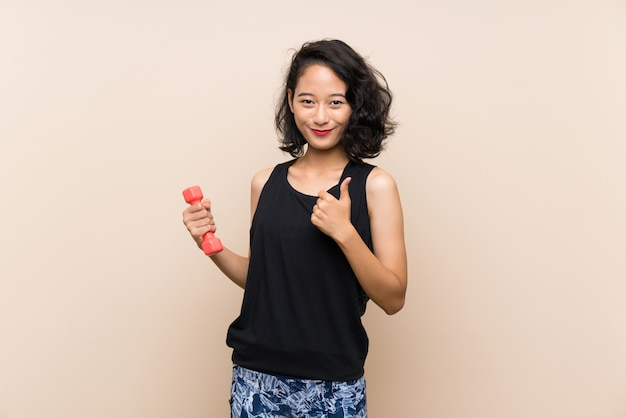 Young asian girl making weightlifting with thumbs up because something good has happened