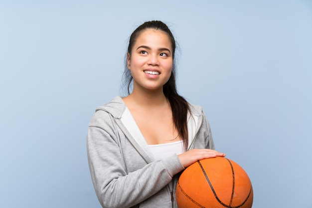 Young asian girl playing basketball over isolated wall looking up while smiling